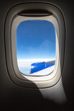 Airplane porthole with view on the airplane wing Royalty Free Stock Image