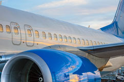 Airplane portholes, engine, tail. At sunset at the airport Stock Images