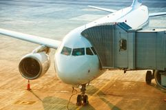 Airplane preparing to take off at the airport, passenger boarding bridge attached to the aircraft Royalty Free Stock Images