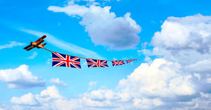 Airplane pulling British flags, union jack Royalty Free Stock Images