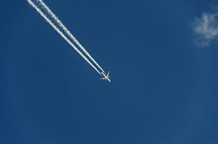 Airplane with reaction trail flying over blue sky with clouds Stock Photography