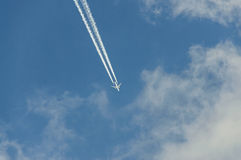 Airplane with reaction trail flying over blue sky with clouds Royalty Free Stock Images