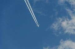 Airplane with reaction trail flying over blue sky with clouds Royalty Free Stock Photo