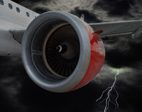 Airplane With Red Engine Flying in Stormy Clouds. Commercial airplane with red engine in flight through stormy rain clouds with flashing lightning. Realistic Royalty Free Stock Photo