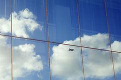 Airplane reflection. Airplane, sky and clouds reflected in the window of a modern office building Stock Image