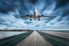 Airplane and road with motion blur effect in overcast. Landscape with passenger airplane is flying over the asphalt road and cloudy sky. Commercial plane is royalty free stock photo