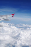 Airplane's wing in blue sky over clouds Royalty Free Stock Images