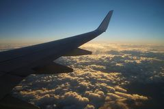 Airplane`s wing with clouds. Flying airplane`s wing with red clouds and sky Stock Image