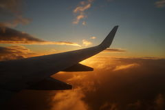 Airplane`s wing with sunset and sky. Flying airplane`s wing with red clouds and sky Royalty Free Stock Images