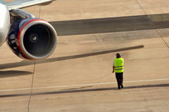 Airplane and safety service.. Airport field engineer is providing safety services and giving orders to the pilots of the big airplane by wire connection. The Royalty Free Stock Photos