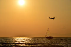 The Airplane and sailboat on sunset background Stock Image