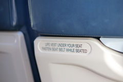 Airplane seat with life vest under your seat text. Airplane seat with life vest under your seat and fasten seat belt text stock photos