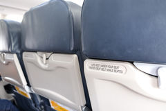 Airplane seat with life vest under your seat text. Airplane seat with life vest under your seat and fasten seat belt text stock photo