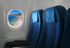 Airplane seat and window. Inside an aircraft with view on sea in Croatia Royalty Free Stock Photo