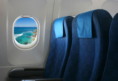 Airplane seat and window. Inside an aircraft with view on sea in Croatia royalty free stock photography