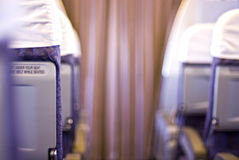 Airplane seats. Looking up the aisle of an airplane, seats and curtain Royalty Free Stock Photos