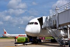 Airplane shipping operations in VietNam Saigon Airport. A Malindo Airlines plane is loading cargoes in VietNam airport, shown as industrial of transportation and Royalty Free Stock Photos