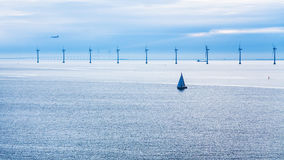 Airplane, ships and bridge near offshore wind farm Stock Image