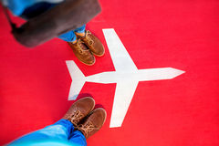 Airplane sign with couple's legs on the red Stock Image