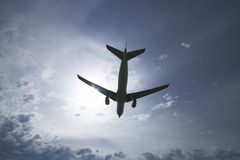 Airplane silhouette. Jet airplane flying over head with the sun and clouds in the background Stock Photography
