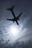 Airplane silhouette. Jet airplane flying over head with the sun and clouds in the background Royalty Free Stock Images