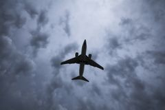 Airplane silhouette. Jet airplane flying over head with clouds in the background Royalty Free Stock Photography