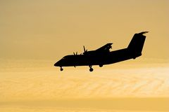 Airplane silhouette. Commuter airplane approaching the airport during sunset Royalty Free Stock Image