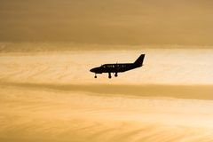 Airplane silhouette. Small airplane landing during sunset Stock Image