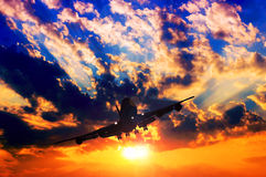 Airplane silhouette. With abstract sunset in the background Stock Photos