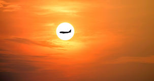 Airplane silhouette on the beautiful sun and red sky. Stock Photography