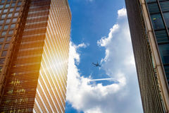 Airplane silhouette with business office towers background.  Stock Images