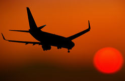 Airplane Silhouette going towards the sun at dusk Royalty Free Stock Photography