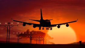 Airplane silhouette landing on sunset. Airplane silhouette of Jumbo Jet lands at the airport during sunset. Shape of airplane and flashing runway lights Stock Image