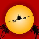 Airplane silhouette over red sky and sun Royalty Free Stock Photos