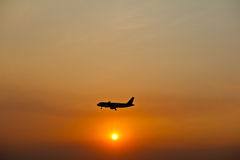 Airplane silhouette over sunset Stock Photo