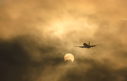 Airplane silhouette. In the sky at sunrise Stock Photography