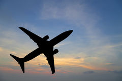 Airplane silhouette in the sky at sunset. Stock Photo
