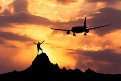 Airplane and silhouette of a standing happy man Royalty Free Stock Photography