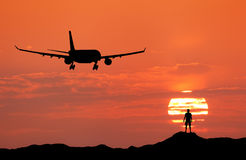 Airplane and silhouette of a standing happy man. On the hill at sunset. Summer landscape with landing passenger airplane. Plane flying in the red sky with Royalty Free Stock Photos