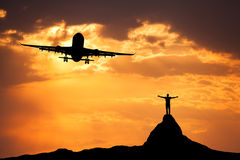 Airplane and silhouette of a standing happy man. With raised-up arms on the mountain peak at sunset. Summer landscape with landing passenger airplane flying in Royalty Free Stock Photo