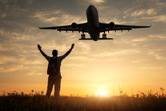 Airplane and silhouette of a standing happy man. With raised-up arms on the at sunset. Landscape with landing passenger airplane flying in the yellow sky with Stock Photography