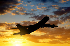 Airplane. Silhouette in the sunset Stock Photos