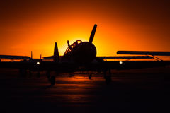 Airplane silhouette at sunset with pilot waving. Airplane silhouette in orange sunset with pilot waving Royalty Free Stock Photo