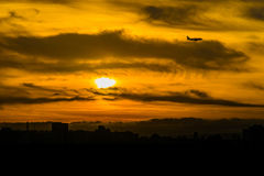 Airplane silhouette on sunset sky background Stock Image