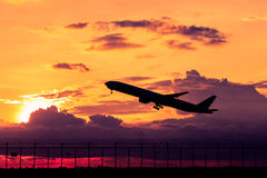 Airplane silhouette. Airplane taking off at sunset. Silhouette of a big passenger or cargo aircraft, airline. Transportation Stock Photos