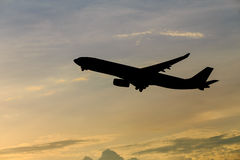 Airplane silhouette. Airplane taking off at sunset. Silhouette of a big passenger or cargo aircraft, airline. Transportation Royalty Free Stock Photo
