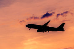 Airplane silhouette. Airplane taking off at sunset. Silhouette of a big passenger or cargo aircraft, airline. Transportation Stock Photo
