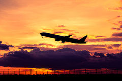 Airplane silhouette. Airplane taking off at sunset. Silhouette of a big passenger or cargo aircraft, airline. Transportation Stock Images