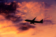 Airplane silhouette. Airplane taking off at sunset. Silhouette of a big passenger or cargo aircraft, airline. Transportation Stock Image