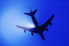 Airplane Silhouetted On Bright Sky stock image
